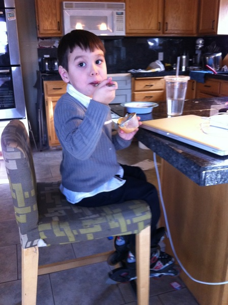 Quinn wearing rollerblades sitting on a barstool eating applesauce with a fork.