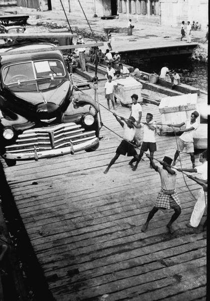 """""""Het aan boord van de 'Bagan' takelen van een auto tijdens de inscheping in de haven van Makassar"""""""