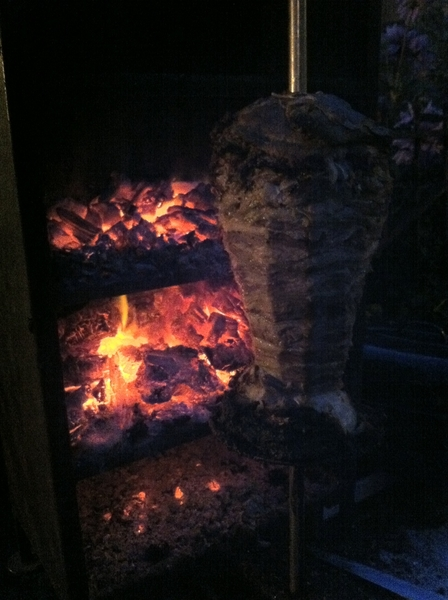 At a friend's backyard party in Chicago eating Pueblan tacos árabes cooked on a spit spinning in front of charcoal
