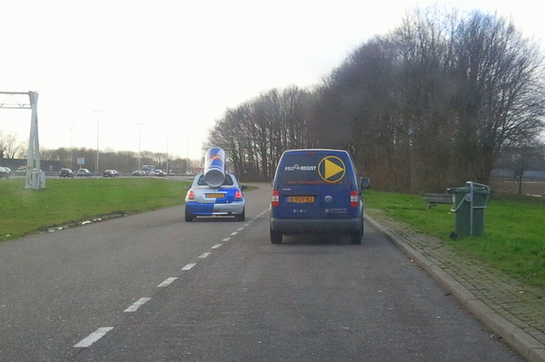 Eén Blik op de weg en één achter de hand - voor vermoeide automobilist op parkeerterrein langs snelweg. Opvallende actie Red Bull @redbull