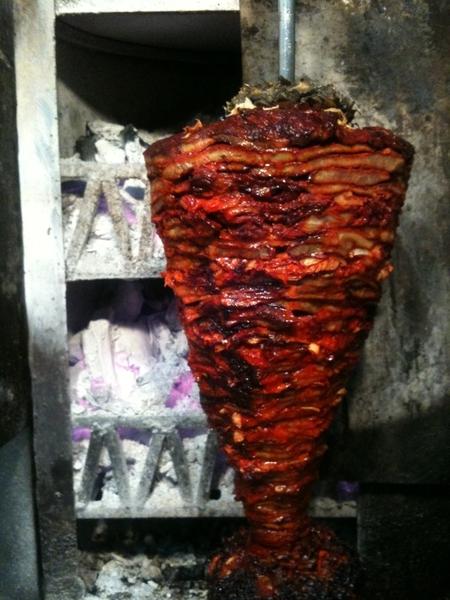 Charcoal-roasted spit of pastor pork for tacos at El Farolito
